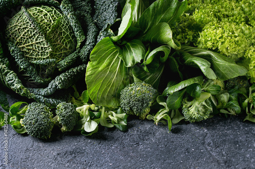 Variety of raw green vegetables salads, lettuce, bok choy, corn, broccoli, savoy cabbage as frame over black stone texture background. Space for text
