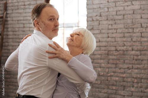 Fotografia Involved aged dance couple waltzing in the dance studio