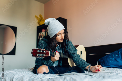 Fototapeta Young beautiful woman composing a song  sitting on her bed in the bedroom holdin