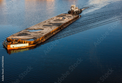Photographie Tugboat pushing barge with sand
