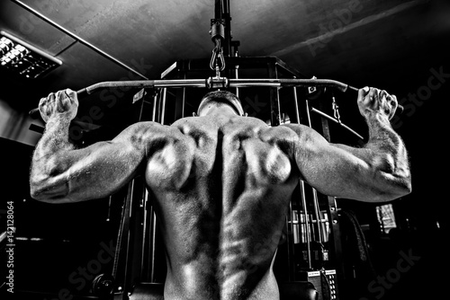 Canvas Print Strong Bodybuilder Doing Heavy Weight Exercise For Back On Machine