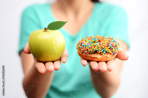 It's hard to choose healthy food concept, with woman hand holding an green apple and a calorie bomb donut