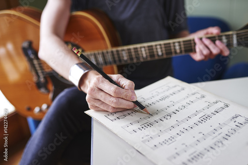 Fotografie, Obraz a person making notes on sheet music and holding a guitar.