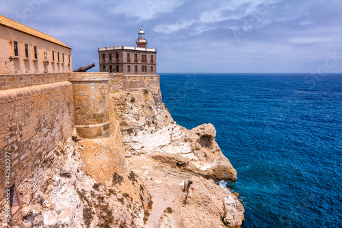 Lighthouse in harbor Melilla, Spanish province in Morocco. The rocky coast of the Mediterranean Sea.