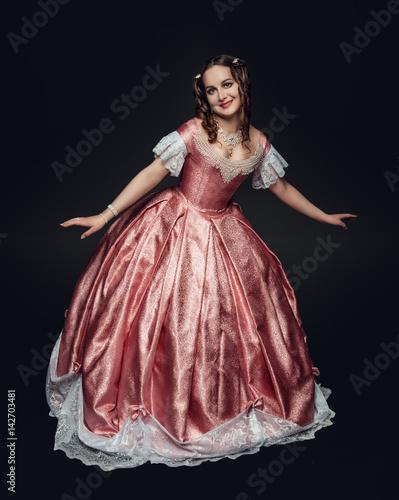 Slika na platnu Young beautiful woman in medieval dress making curtsy on black