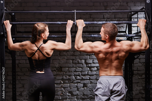 Wallpaper Mural Young attractive caucasian crossfit man and woman working out in gym, rear view,