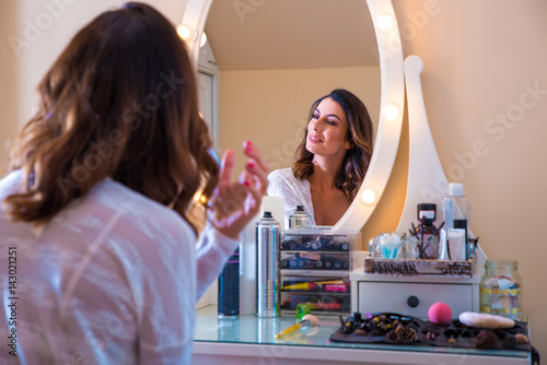 Obraz na płótnie A beautiful young woman at a makeup table