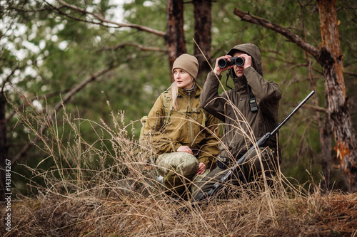 male hunter with binoculars ready to hunt, holding gun and walking in forest.