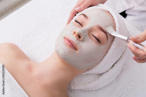Carta da parati Woman gets face mask by beautician at spa