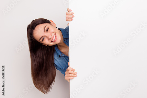 Slika na platnu Young smiling long-haired girl standing and appear  near big poster,  place for