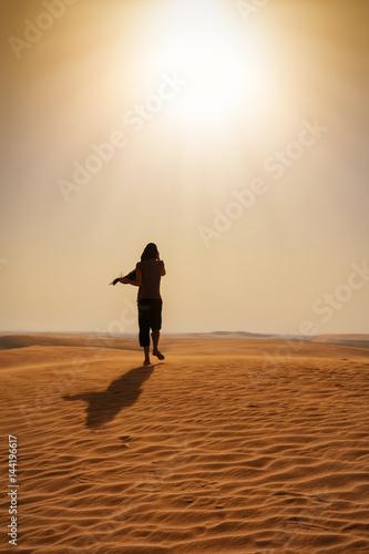 Frau mit schwarzem Schleier läuft in einer Wüste in Katar Wall mural