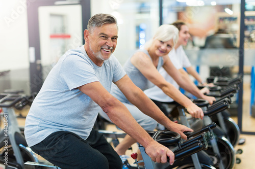 Obraz na plátně Confident seniors on exercise bikes in spinning class at gym