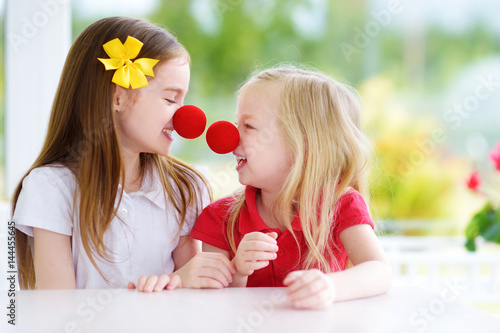 фотография Happy little sisters wearing red clown noses having fun together on sunny summer