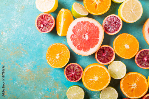 Foto Citrus fruits on turquoise abstract background