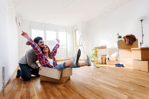 Happy young couple moving in new home unpacking boxes