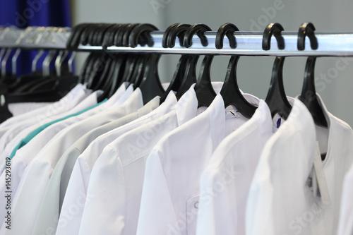 Obraz na plátně Medical uniform on a hangers in a shop