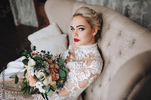 Carta da parati Beautiful bride in a lace dress with an original wedding bouquet in a vintage interior