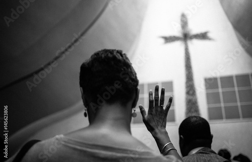 Photo A black woman crosses her fingers in the church.