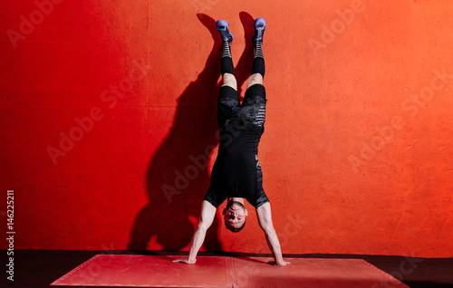 Athlete doing push ups on his hands while standing upside down near red wall Fototapet