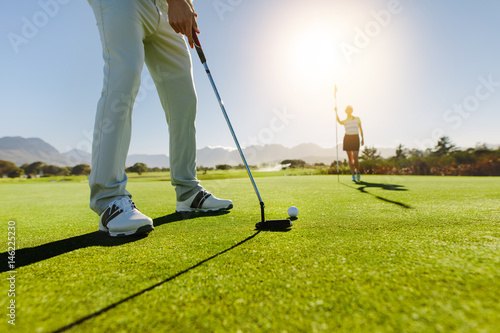 Golfer putting ball with female partner holding flag on golf cou