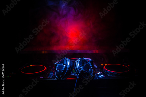 DJ Spinning, Mixing, and Scratching in a Night Club, Hands of dj tweak various track controls on dj's deck, strobe lights and fog, selective focus, close up. Dj Music club life concept