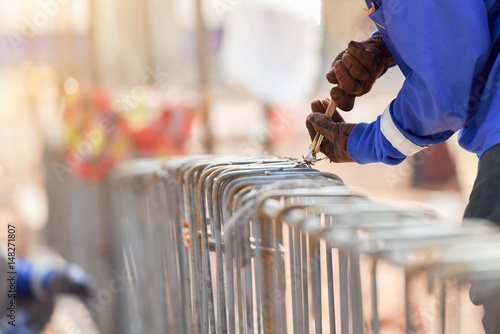 Stampa su Tela Construction workers hands using steel wire construction and pincers to secure r