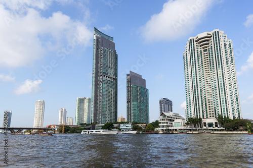 Tall and modern skyscrapers along the Chao Phraya River in Bangkok, Thailand.