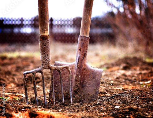 shovel and pitchfork in soil in spring garden, shallow depth of field, toned, lo Fototapet
