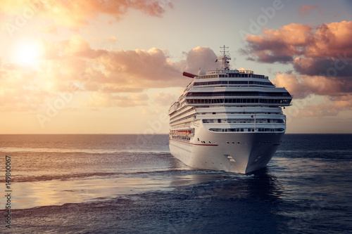Luxury cruise ship leaving port at sunset