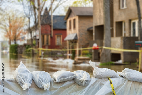 Fotografia, Obraz Close shot of flood Protection Sandbags with flooded homes in the background