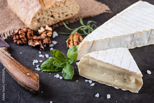 Fresh brie cheese with ciabatta on dark stone background