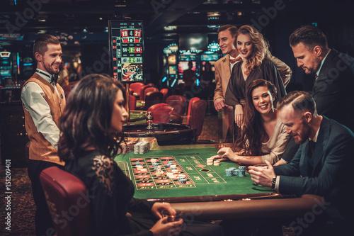 Leinwand Poster Upper class friends gambling in a casino