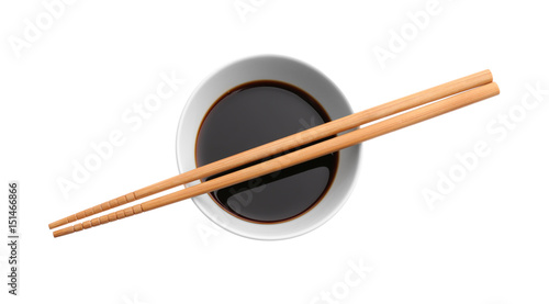 Bowl with tasty soy sauce and chopsticks on white background