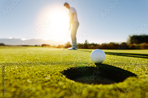 Man puts the ball on golf course green