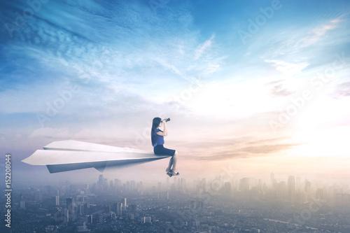 Businesswoman sitting on paper aeroplane