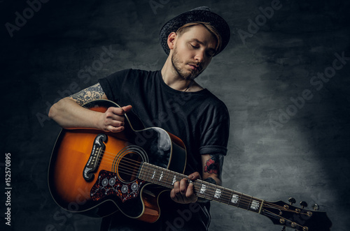 Fotografia Handsome young acoustic guitar blues player with tattoos on arms.