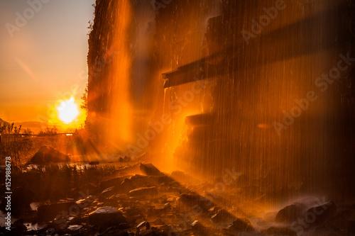 The sun illuminates the waterfall at sunset. Norway