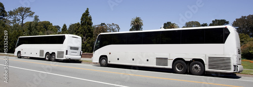 Fotografia Two parked white charter sightseeing buses with tinted windows under blue sky