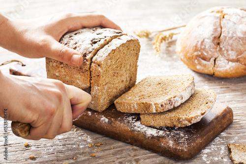 Fényképezés Female hands cutting whole wheat bread