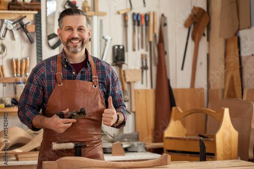 Happy Carpenter/Middle ages handsome carpenter finished creating cabriolet legs Fototapet