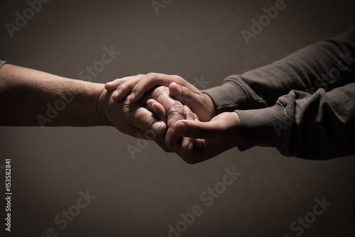 Child hands holding senior woman's hands on brown background Fototapet