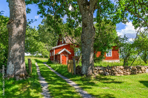 Fototapeta Red cottage in a rural idyll