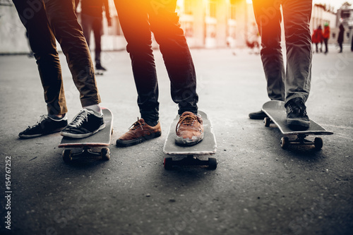 Photo Group of friends skateboarders rest on the street and skateboard