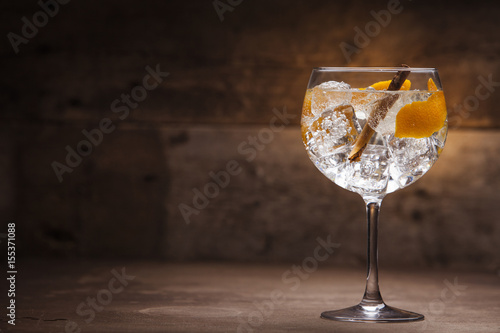 Gin and tonic cocktail on a wooden table with background