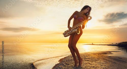 Stampa su Tela Beautiful young woman in bikini with sax on sea shore on sunset background