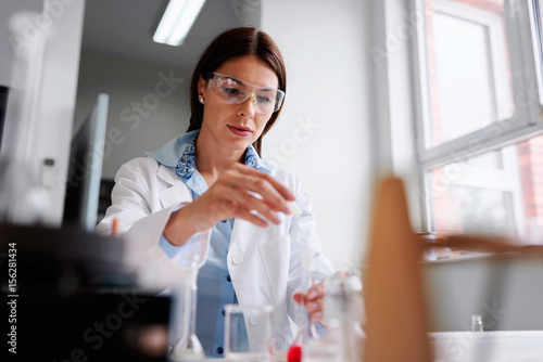 Fotografiet Woman scientist carrying out experiment in research laboratory