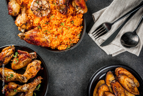 West African national cuisine. Jollof rice with grilled chicken wings and fried bananas plantains.On gray stone table. Copy space  top  view