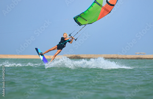 Kite surfing girl in sexy swimsuit with kite in sky on kiteboard in the blue sea jumping kiteboarding trick. Recreational activity, water sports, action, hobby, fun in summer time. Kiteboarding sport