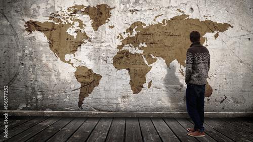 Obraz na plátne Jeune homme devant mur-planisphère