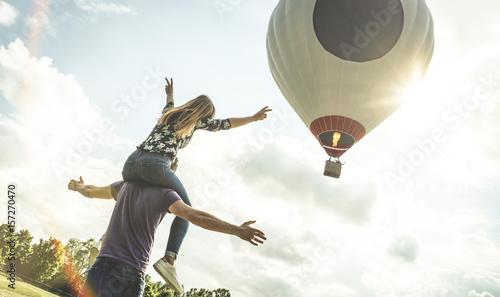 Fotografia Happy couple in love on honeymoon vacation cheering at hot air balloon - Summer